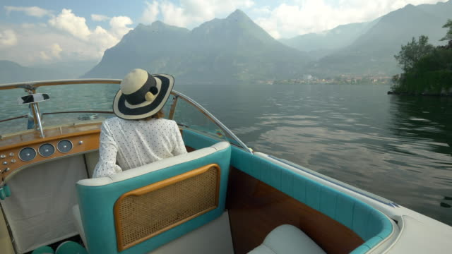 a woman on a classic luxury wooden runabout boat on an italian lake. - slow motion - wake water stock videos & royalty-free footage