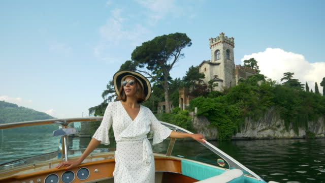 a woman on a classic luxury wooden runabout boat on an italian lake. - slow motion - wealth stock videos & royalty-free footage