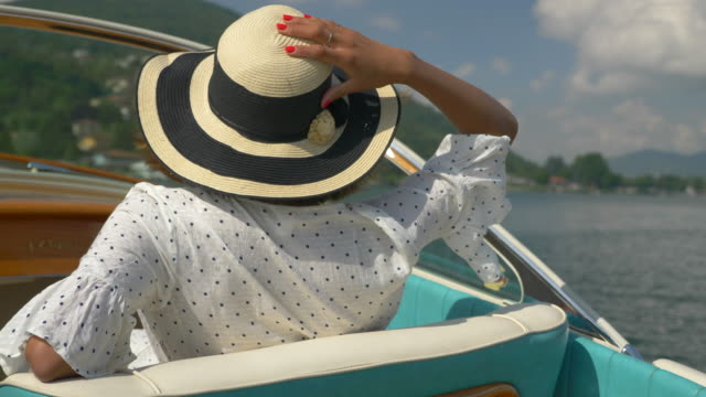 a woman on a classic luxury wooden runabout boat on an italian lake. - slow motion - small boat stock videos & royalty-free footage