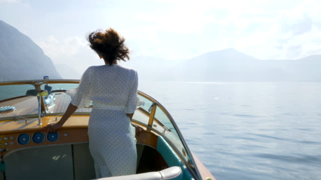 a woman on a classic luxury wooden runabout boat on an italian lake. - slow motion - eleganz stock-videos und b-roll-filmmaterial