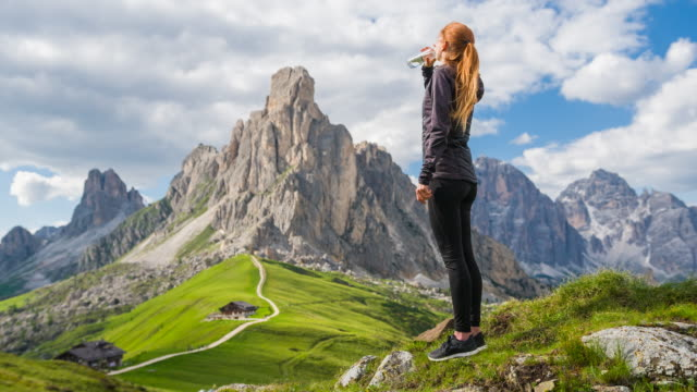 woman on a grass meadow drinking water, view of mountains in background - cold drink stock videos and b-roll footage