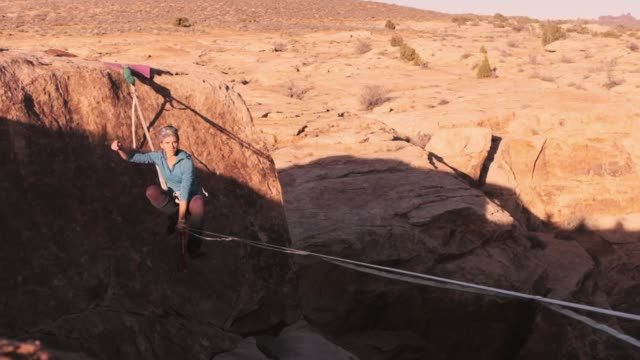 woman on a high line rope in moab utah - tightrope walking stock videos & royalty-free footage