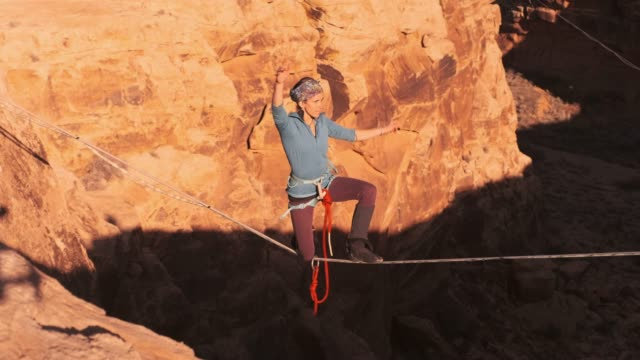 woman on a high line rope in moab utah - conquering adversity stock videos & royalty-free footage