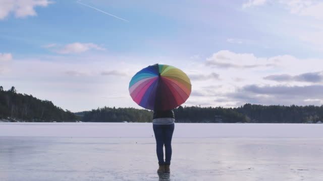 woman on a icy lake with rainbow umbrella - umbrella stock videos and b-roll footage