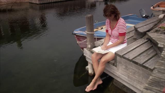 a woman on a  jetty reading a newspaper huvudskar stockholm archipelago sweden. - summer reading stock videos & royalty-free footage