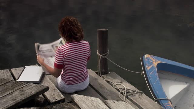 a woman on a  jetty reading a newspaper huvudskar stockholm archipelago sweden. - lesen stock-videos und b-roll-filmmaterial