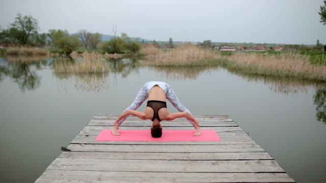 Woman on a lake doing a headstand on a yoga mat