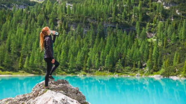 woman on a mountain rock next to a beautiful lake drinking water - reusable stock videos & royalty-free footage