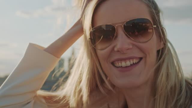 donna su un tetto. flirtare con la fotocamera - capelli biondi video stock e b–roll