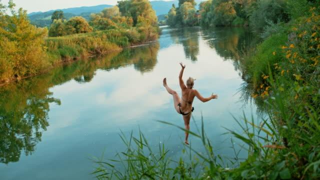 vídeos y material grabado en eventos de stock de time warp woman en un columpio de cuerda saltando al río - agua estancada