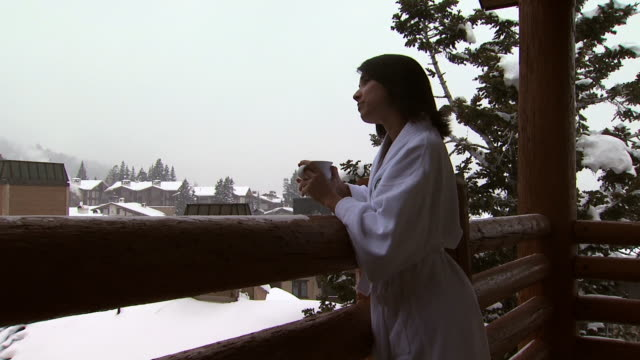 a woman on a snowy balcony drinking coffee - see other clips from this shoot 1169 stock videos & royalty-free footage