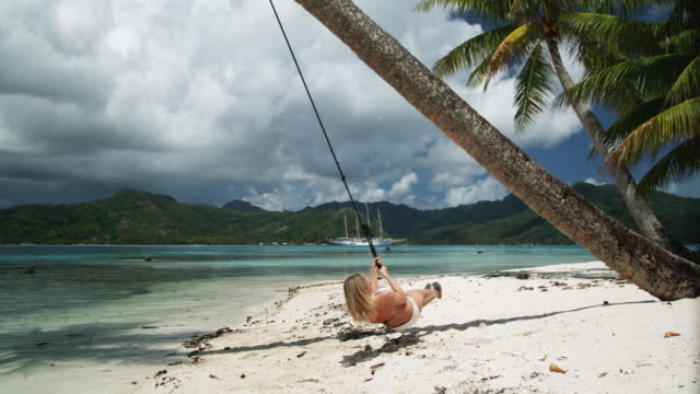 woman on a swing on the beach - isola di tahaa video stock e b–roll
