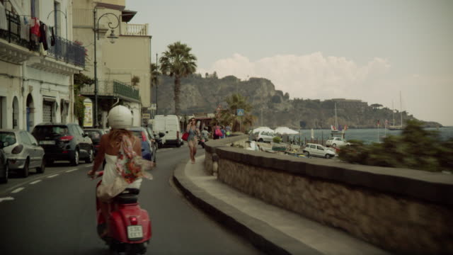 a woman on a vespa drives along the coast - motorino video stock e b–roll