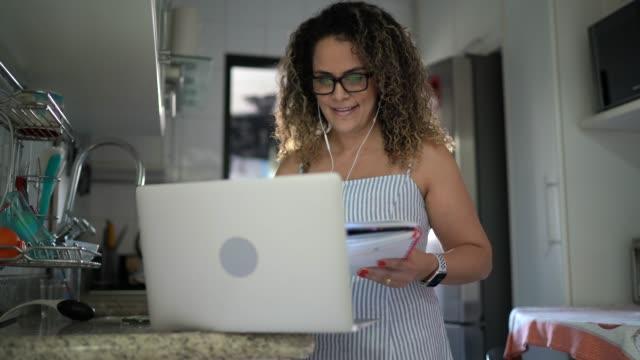 vídeos de stock, filmes e b-roll de mulher em uma chamada de vídeo, trabalhando em casa e tomando notas - cozinha doméstica