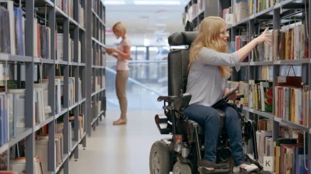 vídeos y material grabado en eventos de stock de ds mujer en silla de ruedas en biblioteca hallazgo derecha reservar en el estante - biblioteca