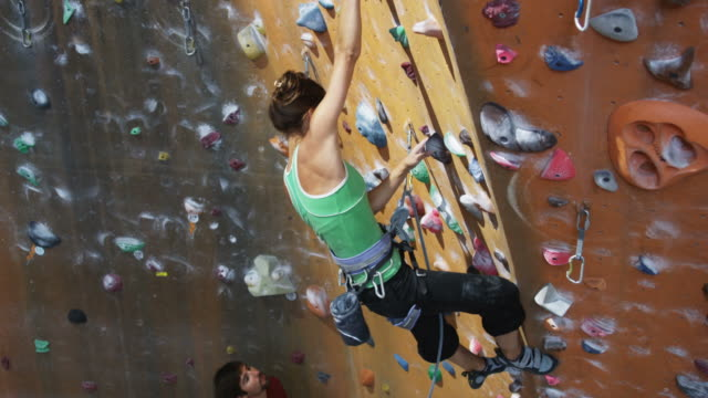 woman on an indoor climbing wall as a man belays below - kletterwand kletterausrüstung stock-videos und b-roll-filmmaterial