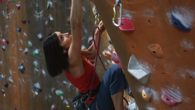 woman on an indoor climbing wall - kletterwand kletterausrüstung stock-videos und b-roll-filmmaterial