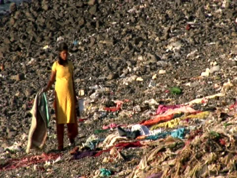 woman on banks of river sifting through rubbish, zoom out to city, mumbai, india - hygiene stock videos and b-roll footage