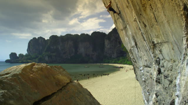 tu ws woman on beach belays for rock climber hanging from rock face/ krabi, thailand - rock face stock videos & royalty-free footage