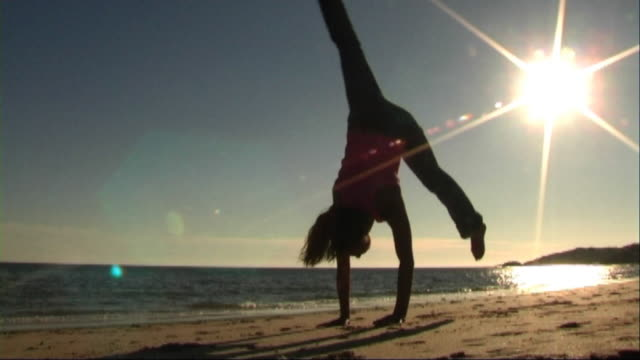 woman on beach doing acrobatics - londonalight stock videos and b-roll footage