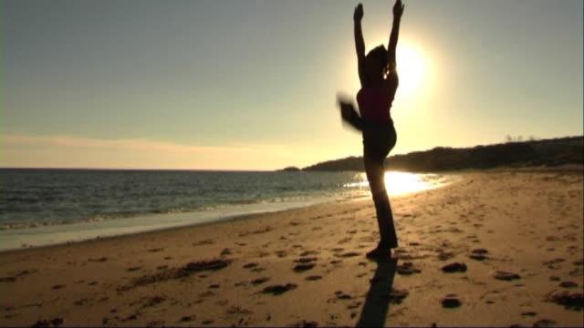 vidéos et rushes de woman on beach doing acrobatics - seulement des jeunes femmes