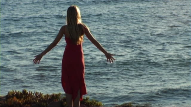 vidéos et rushes de woman on beach stretching out arms to the sea - membres du corps humain