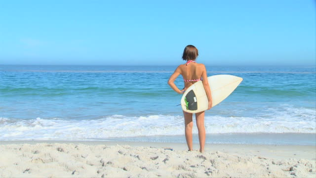 Woman on beach with surf board / Cape Town, Western Cape, South Africa