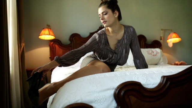 woman on bed removing high heel shoes - eleganter schuh stock-videos und b-roll-filmmaterial