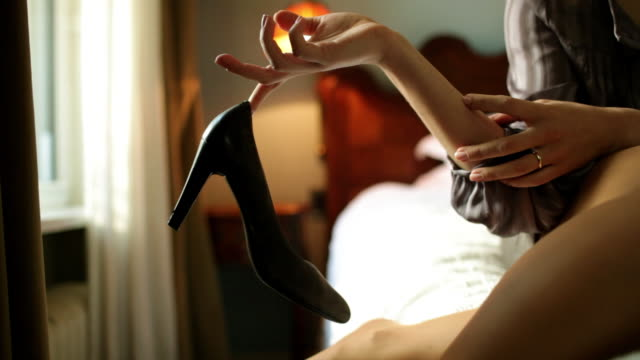 Woman on bed removing high heel shoes