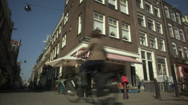 ms, la, woman on bicycle riding past fruit and vegetable shop, amsterdam, netherlands - ecke eines objekts stock-videos und b-roll-filmmaterial