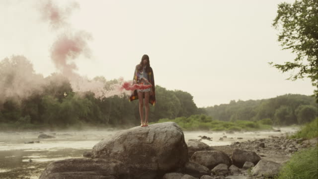 Woman on big rock in nature with red smoke around her
