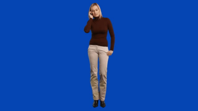 ws woman on blue screen talking on phone - full length stock-videos und b-roll-filmmaterial