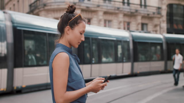 woman on city street with phone and train passing by - reportage stock videos & royalty-free footage
