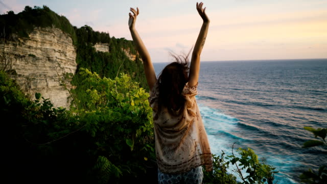 woman on cliff with view on  ocean in bali - clima tropicale video stock e b–roll