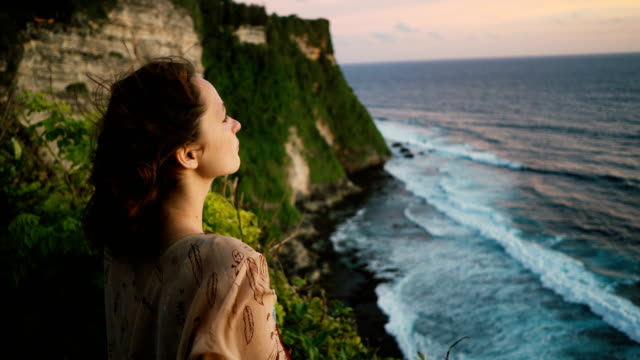 woman on cliff with view on  ocean in bali - cliff stock videos & royalty-free footage