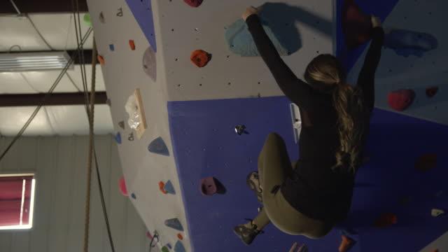 vídeos y material grabado en eventos de stock de woman on climbing wall dropping down to mat - escalada libre