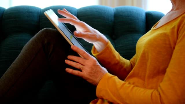 vídeos y material grabado en eventos de stock de mujer en sofá con tableta digital - mesa baja de salón