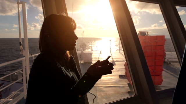 Woman on ferry boat using a mobile phone