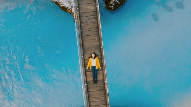 aerial ms ws woman on footbridge in valley - exploration stock videos & royalty-free footage