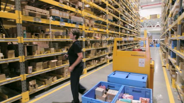 vídeos de stock e filmes b-roll de woman on forklift picking boxes from racks in warehouse - objeto manufaturado