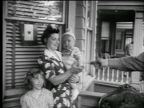 b/w 1944 woman on front porch holding baby with daughter standing by being handed envelope - postal worker stock videos & royalty-free footage