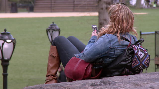 vídeos de stock, filmes e b-roll de woman on her cell phone laying on a rock in central park - jaqueta jeans