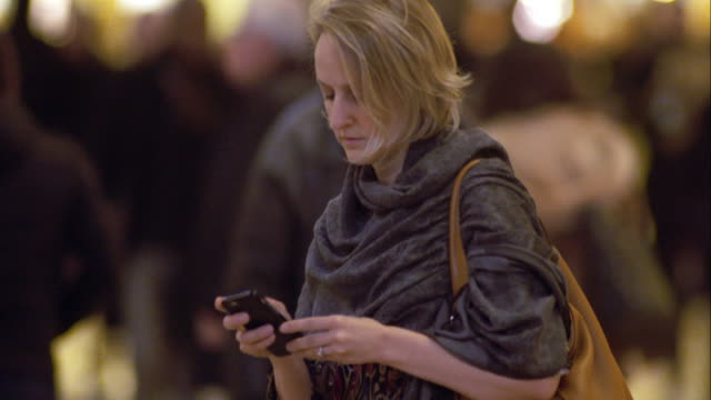 Woman on Her Cellphone as Commuters Pass Around Her in Grand Central Terminal in Manhattan