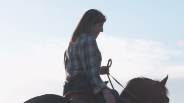 frau auf ihrem pferd reiten tilt von stiefeln gesicht sonne flackert das objektiv - in den vierzigern stock-videos und b-roll-filmmaterial