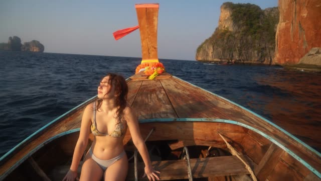 vídeos de stock e filmes b-roll de woman on long-tail boat near koh phi phi island - ilhas phi phi
