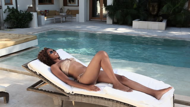 woman on lounger, man diving into pool - solstol bildbanksvideor och videomaterial från bakom kulisserna