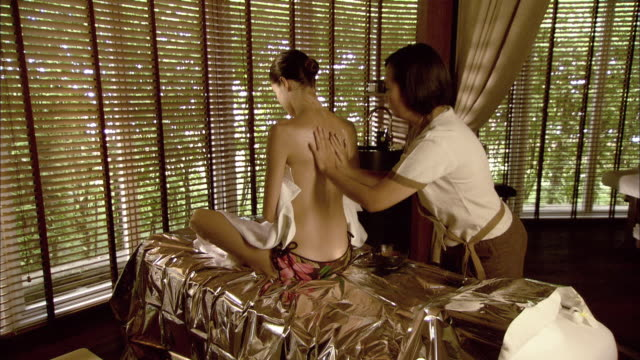 ms woman on massage table has herbal mud rubbed into her back and shoulders, hua hin, prachuap khiri khan, thailand - massage table stock videos & royalty-free footage