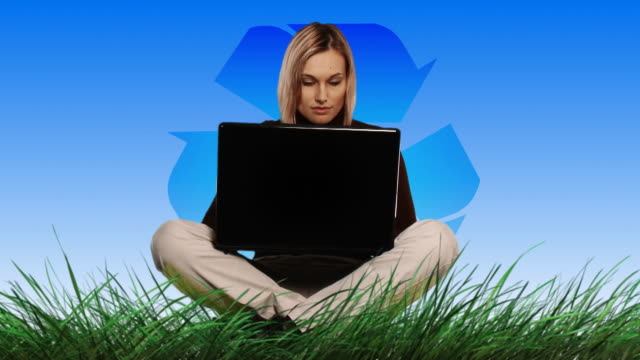 montage ws woman on meadow with laptop and recycling symbol - societal symbol stock videos & royalty-free footage