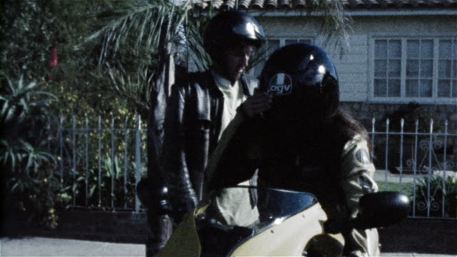 vídeos de stock e filmes b-roll de woman on motorcycle closing visor on helmet / man getting on motorcycle behind woman / taking off - sentar se