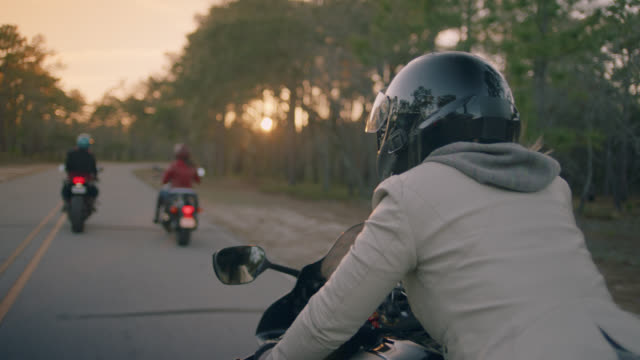 slo mo. woman on motorcycle cruises with friends down wooded country road. - motorradfahrer stock-videos und b-roll-filmmaterial
